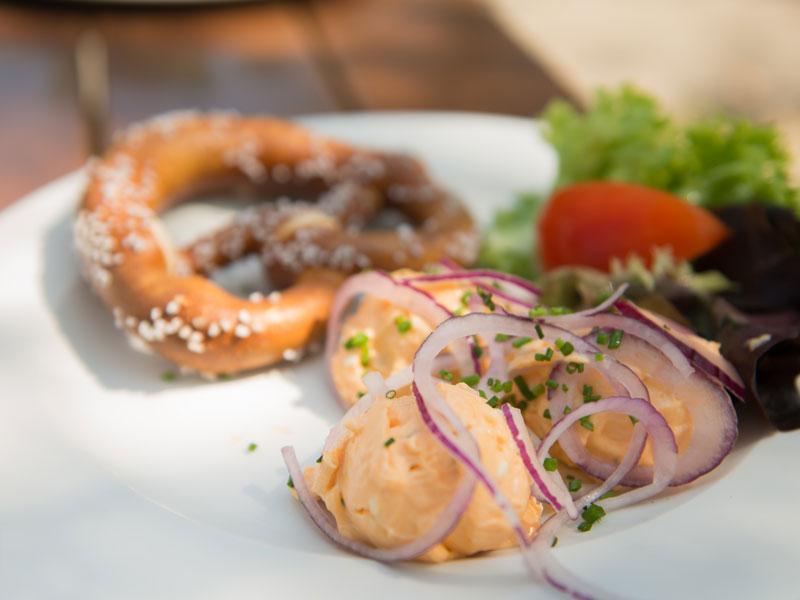 Portion Obazda mit Zwiebelringen, Salatgarnitur und Brez'n