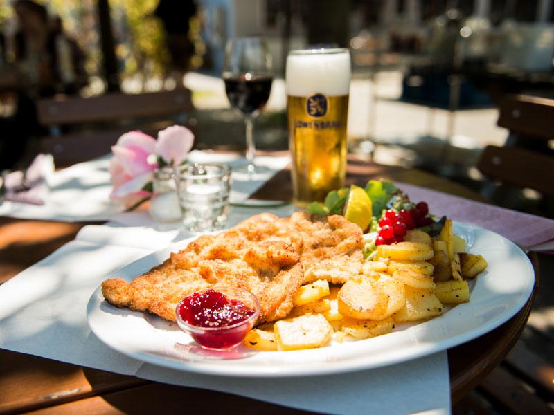 Schnitzel Wiener Art von der Schweinelende, mit Bratkartoffeln und Salaten der Saison